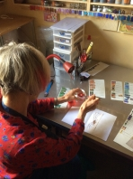 Harriet sifting powdered enamel onto a hand cut stencil over a copper leaf.